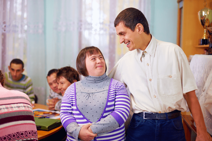 Man standing and smiling to a woman with Down Syndrome